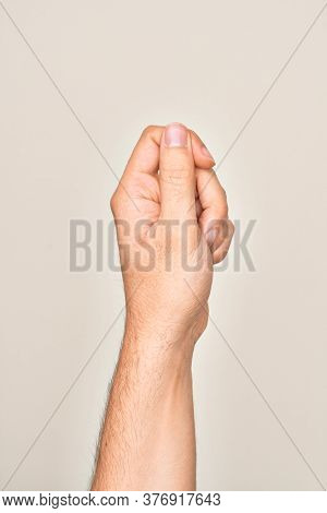 Hand of caucasian young man showing fingers over isolated white background holding blank space with thumb finger, business and advertising