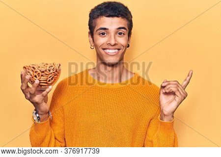 Young african amercian man holding pretzels smiling happy pointing with hand and finger to the side
