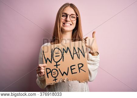 Young beautiful redhead woman asking for women rights holding banner over pink background happy with big smile doing ok sign, thumb up with fingers, excellent sign