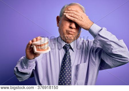 Grey haired senior man holding orthodontic prosthesis denture over purple background stressed with hand on head, shocked with shame and surprise face, angry and frustrated. Fear and upset for mistake.