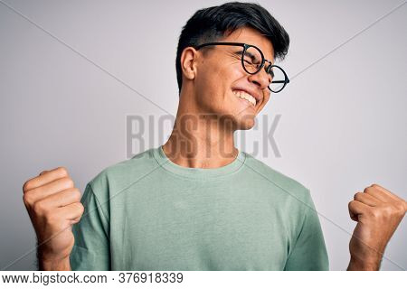 Young handsome man wearing casual t-shirt and glasses over isolated white background very happy and excited doing winner gesture with arms raised, smiling and screaming for success. Celebration