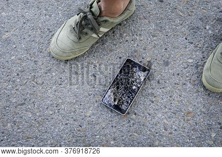 Phone With Broken Screen On Asphalt. Someone Dropped Device. Broken, Destroyed, Ruined Modern Mobile