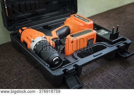 Cordless Orange Drill With Black Battery. Orange Screwdriver Or Drill In Black Container Lies On The