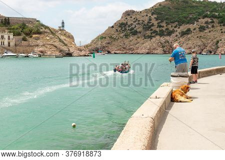 Balaklava, Sevastopol, Crimea - July 8, 2020: A Motor Boat With Fishermen Sails Out Of The Bay Into