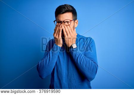 Young handsome man with beard wearing casual sweater and glasses over blue background rubbing eyes for fatigue and headache, sleepy and tired expression. Vision problem
