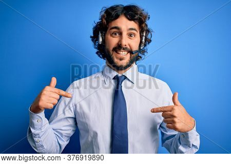 Young handsome call center agent man with beard working using headset over blue background looking confident with smile on face, pointing oneself with fingers proud and happy.