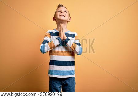 Young little caucasian kid with blue eyes wearing colorful striped shirt over yellow background begging and praying with hands together with hope expression on face very emotional and worried. Begging