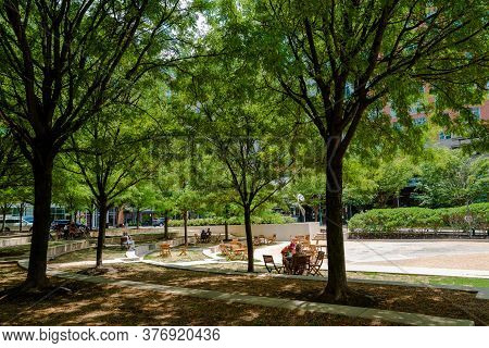 Reston, Va, Usa -- July 17, 2020.  People In Reston Town Center Park Are Socially Distanced Under Th