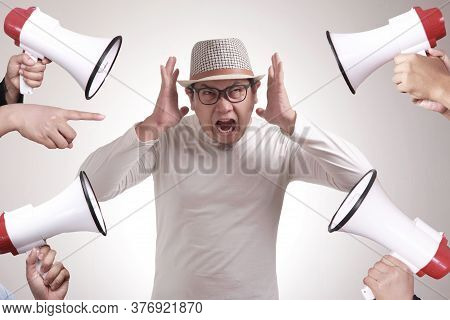 Young Asian Man Covered His Ear Ignoring Noise. Stressed Under Pressure Concept