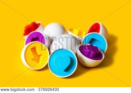 Multicolored Plastic Eggs On Yellow Background. An Educational Sorter Toy For Toddler To Recognize A