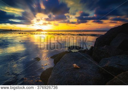 Long Exposure Seascape And Rocky Beach Against Sunset Background. Nature Composition With Soft And G