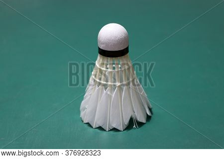 Used Shuttlecock Put Vertical On Green Floor Of Badminton Court. Badminton Sport Concept.