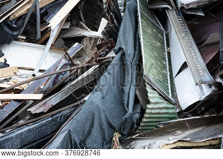 Close-up Shot Of Construction Debris In The Wake Of A Demolition. Broken Wooden Planks, Torn Fabric