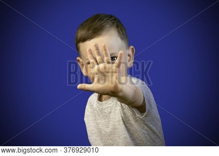 A Boy In A Gray T-shirt Put His Hand Forward And Covered His Face With His Palm. The Child Hid Behin