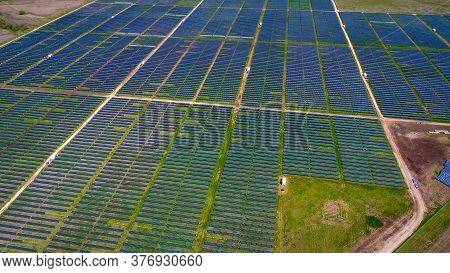 Aerial Drone Views Above Solar Panel Farm Producing Clean Renewable Energy Summer Green Grass And Bl