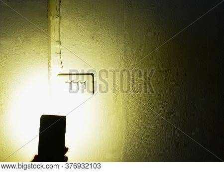 Flashlight Of Mobile Phone Spreading Light  To Electric Switch On Home Wall While Power Outage In Da