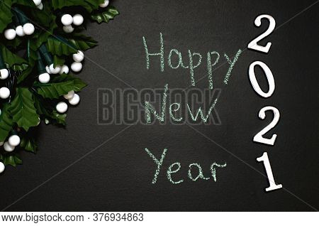 Handwritten Lettering On Black Chalkboard Happy New Year. Christmas Lights On A Black Textured Board