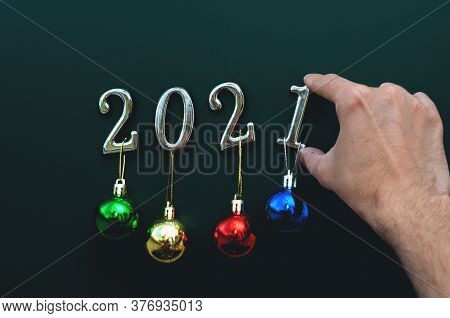 Silver Numbers 2021 With Colorful Balls On A Green Background With Decorations. New Year Concept, Me