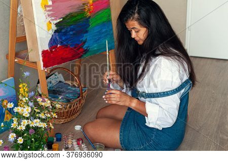 Creative Pensive Female Painter Paints A Colorful Abstract Picture. Closeup Of Painting Process In A