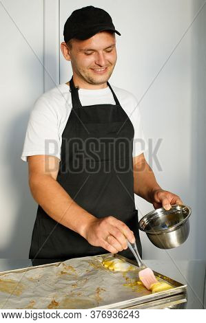 A Young Baker Greases The Dough Before Baking