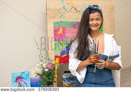 Girl Holding Dirty Painting Brushes In Hands With Picture On Background. The Artist Finished The Abs