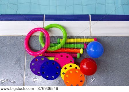 Colored Toys For Swimming And Diving Training Lie On The Side Of The Pool.
