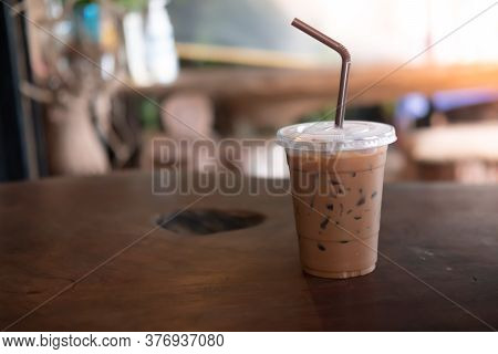 Iced Mocha Coffee In Plastic Glass On Wood Table
