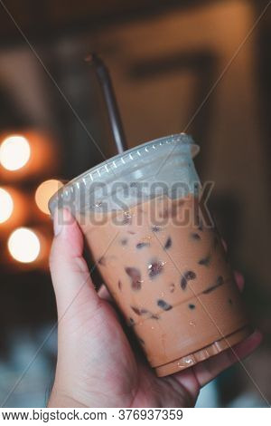Hand Hold Iced Mocha On Light Blur Background. Refreshing Drink
