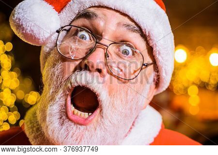 Bearded Man In Santa Hat Holds Broken Eyeglasses. Christmas. Santa Man With Broken Glasses. Surprise