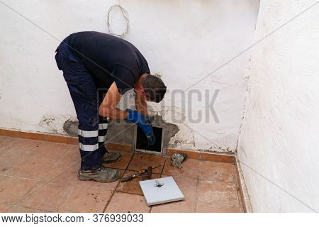 July 13, 2020. Granada. Spain: Worker Cleans The Drains Hatch And Removes Dirt And Debris From The S