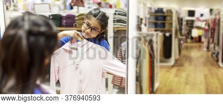 Little Girl Tried Clothes In Front Of Mirror In Shopping Mall. Asian Girl Smileing Happy To Choice A