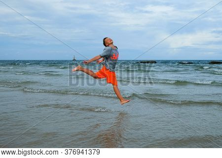 Cute Boy Jumping Up High With Happy Face On Shallow Water Beach On Rainy Day. Joyful Kid Laughing An