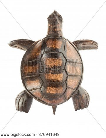 Wooden Figurine Of A Sea Turtle Isolated On A White Background. View From Above.