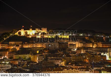 Night View Of Old Town And Sao Jorge Castle From Sao Pedro De Alcantara Viewpoint, In Lisbon, Portug