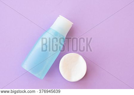 Top View Of Facial Toner And Round Cotton Pads On Purple Background With Copy Space. Blue Liquid Ton