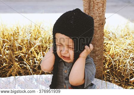 Autumn Portrait Of 2-3 Years Old Child Crying In Garden. Fall Season. Unhappy Mixed-race Baby Boy In