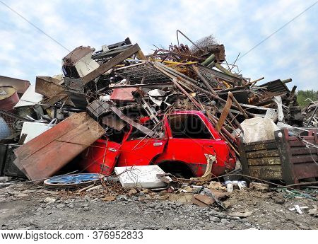 Retro Red Vehicle At Junk Yard. Broken Steel Garbage, Vintage Automotive Parts And Iron In Heap Wast