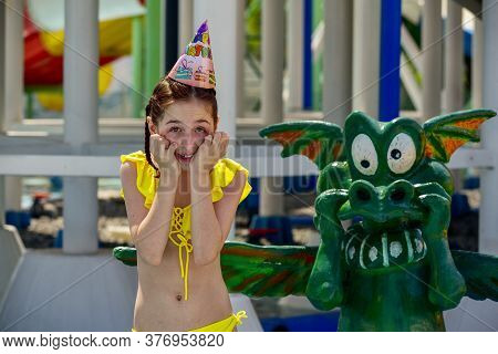 Young Girl At A Waterpark. Girl Wearing A Birthday Cap At The Water Park. A Teenager On His Birthday