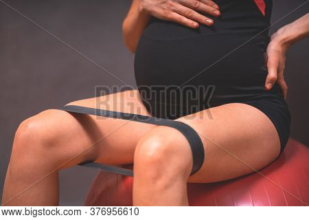 Young Pregnant Woman Exercises With Red Fitball And Dumbell. Working Out And Fitness, Pregnancy Conc