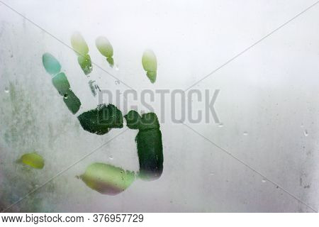 Hand Mark On Condensation Glass Of Window, Right Handprint With Raindrops On Window With Blurred Bac