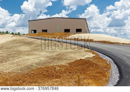 Horizontal Shot Of Fresh Blacktop Leading To A Newly Constructed Commercial Structure.