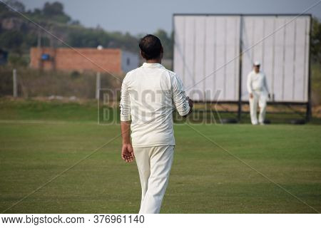 Full Length Of Cricketer Playing On Field During Sunny Day, Cricketer On The Field In Action, Player