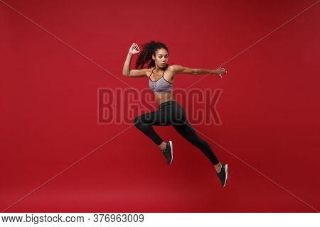Side View Of Young African American Fitness Woman In Sportswear Posing Working Out Isolated On Red W