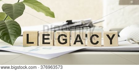 Word Legacy. Wooden Small Cubes With Letters Isolated On White Background With Copy Space Available.