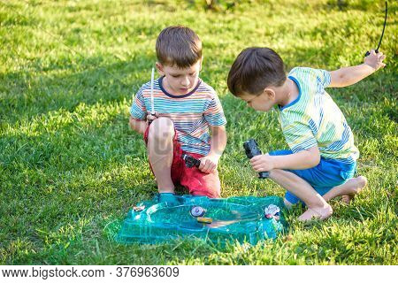 Two Boys Playing With A Spinning Top Kid Toy. Popular Children Game Tournament.