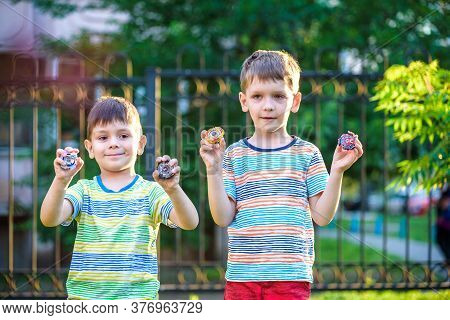 Two Boy Playing With A Spinning Top Outdoors