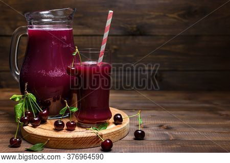 Homemade Fresh Cherry Juice In A Glass And Pitcher With Ripe Sour Cherries On Wooden Table. Selectiv