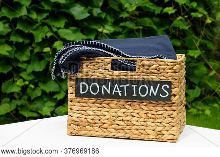 Donation Box For Clothing Donations On A Greenery Background. Charity And Donation Concept. Copy Spa