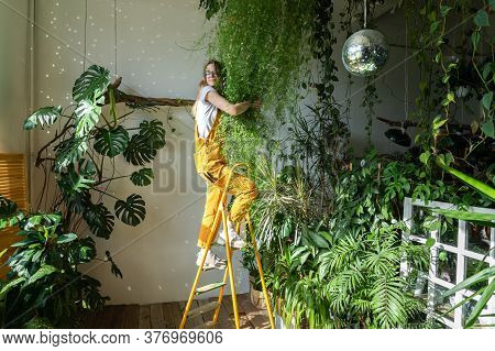 Joyful Young Woman Gardener In Orange Overalls Standing On A Stepladder, Embracing Lush Asparagus Fe
