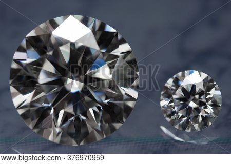 Big And Small Carat Diamond Gemstones On Reflected Table